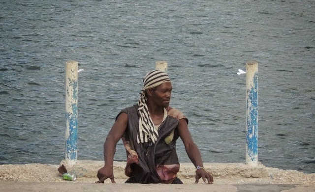 Young man in sleeveless top beside the water in Havana