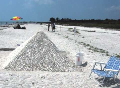 sand pyramid with shells on the beach