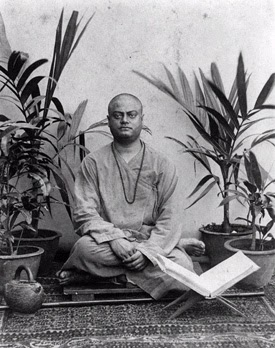 Swami Vivekananda is seated on his sadhu's seat with traditional water jug and a sacred text