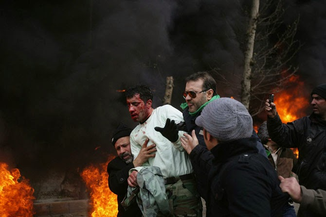 Гражданские защищают избитого демонстрантами иранского полицейского во время протестов в Тегеране, 2009 год.