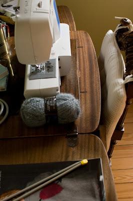 Vue sur plan de travail - pelote de laine, aiguilles, machine à coudre Brother
