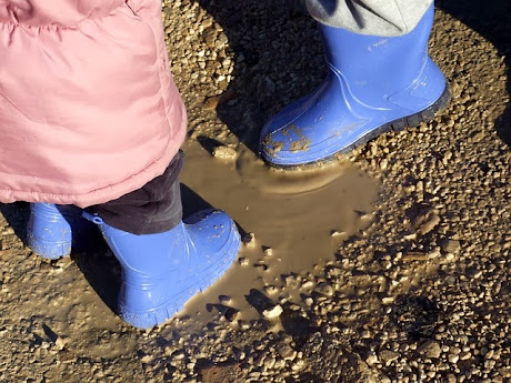 namc montessori sensorial work with soil exploring earth children's boots in mud puddle