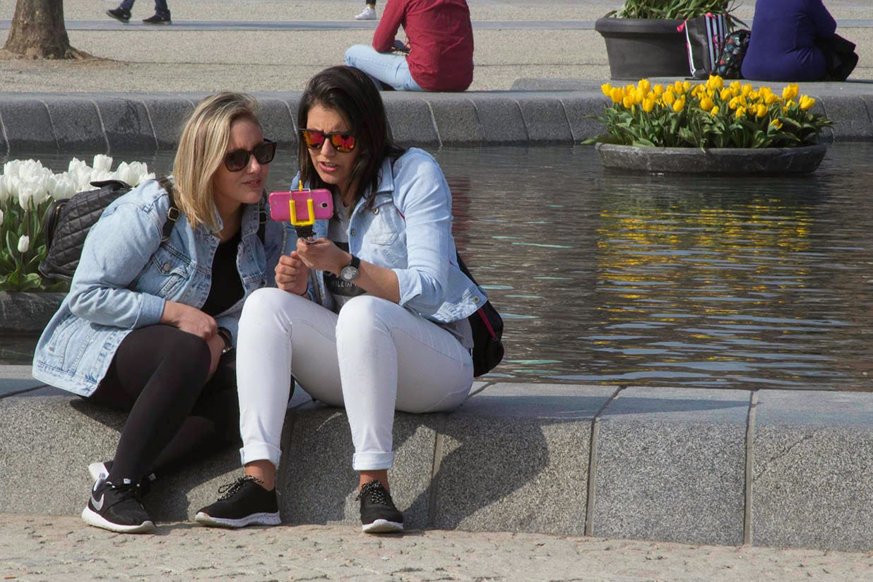 two women with pink cell phone and selfie stick