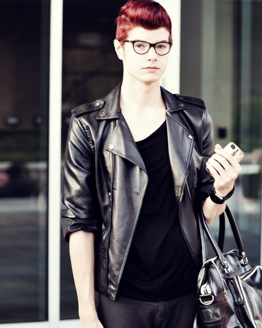 SCAD male student wears a black leather jacket, a black scoop neck tee, black jeans, black bag murse black glasses and black zip-up boots with red hair.