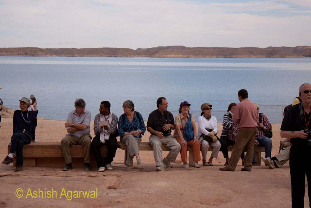 Tourists sitting on a bench near the water of Lake Nasser next to the Abu Simbel temple in Egypt