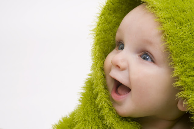 after bath baby picture under green towel and smiling widely