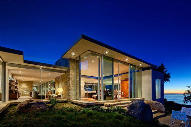 Night View of the Home with Wide Glass Walls and the Bright Lighting