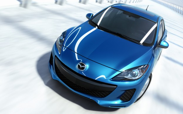 Overhead shot of blue 2012 Mazda 3 Skyactiv crossing a bridge
