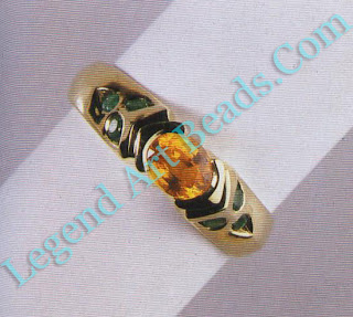 Ring with yellow sapphire and small emeralds.