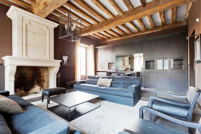 den with white molded fireplace, dark wood floors, exposed beams, dark blue dueling sofas separated by coffee table, a light gray rug, and dark wood cabinets