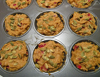 Muffin Tins Filled with Batter and Topped with Pumpkin Seeds