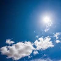 Color photo of blue sky, a few white clouds, and bright sun