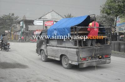 Mobil lewat di jalanan penuh debu yang dimuntahkan dari Gumung Merapi.  Anda harus menutup hidung anda dengan masker demi kesehatan.  Foto Dokumentasi Asep Haryono