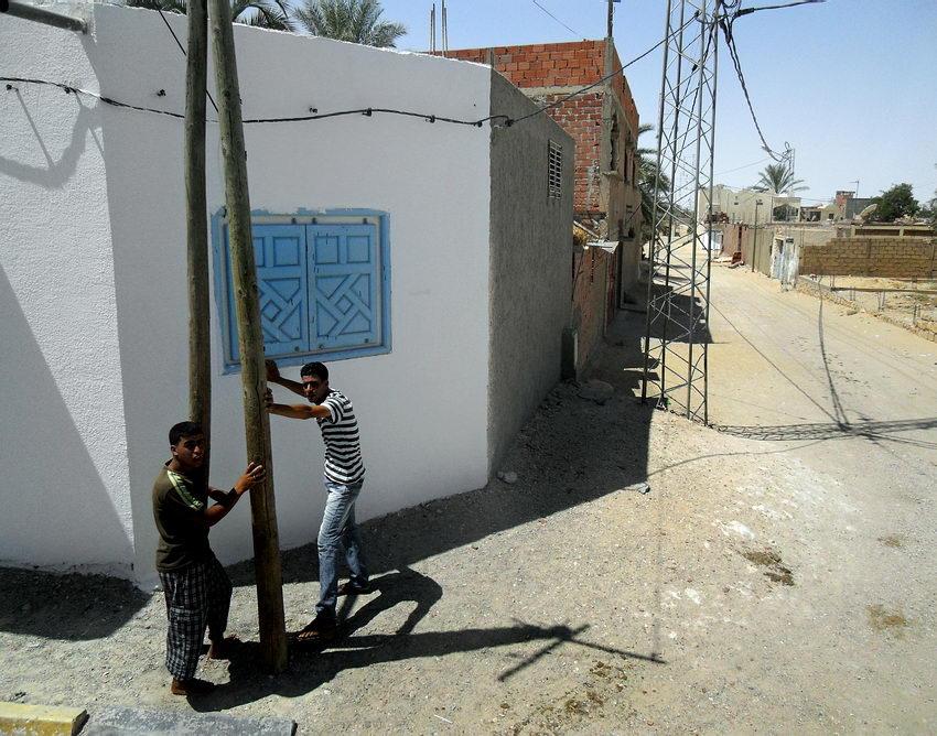 Foto de dois rapazes com as mãos em postes, parecendo que os estão a segurar. À direita rua de terra com construções inacabadas