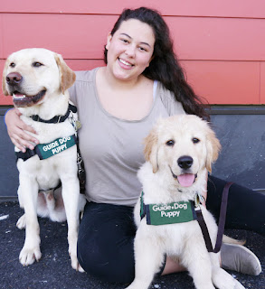 Delphine smiles with a yellow Lab and Golden Retriever guide dog puppy.