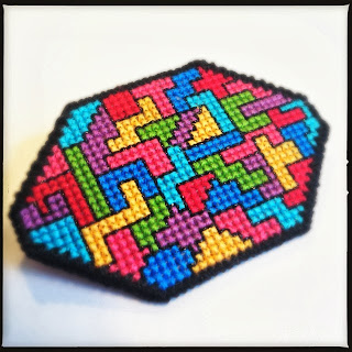 Korssting broderet broche i geometrisk mønster. Lavet af plastik kanvas. Cross stitch embroidered broche in geometric pattern.