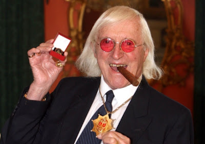 Jimmy Savile receives his knighthood from the Queen for entertainment and services