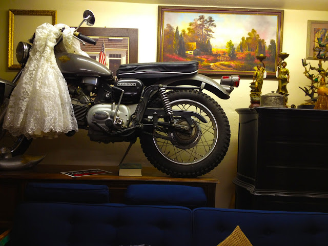 An interesting living room scene including a wedding dress on a motorcycle on a table behind a couch.