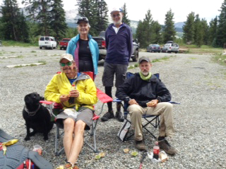 Three Southwest Brighteyes puppy raisers smile with Trevor and Tennille (black Lab) in the wilderness.