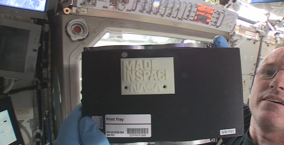 """International Space Station Commander Barry """"Butch"""" Wilmore holds up the first object made in space with additive manufacturing or 3-D printing. Wilmore installed the printer on Nov. 17, 2014, and helped crews on the ground with the first print on Nov. 25, 2014. Image Credit: NASA"""