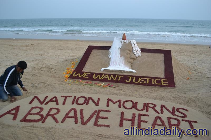 "A sand sculpture on Delhi victim with a message ""We want Justice"" at Puri beach of Odisha by sudarsan Pattnaik"