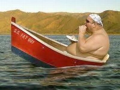 Homem muito gordo comendo enquanto está dentro de um barco minúsculo.