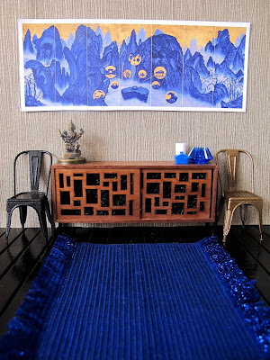 Modern dolls' house miniature scene showing a blue and gold modern chinese panel on the wall. Underneath is a sideboard with a variety of blue and gold items on it, and beside it, two french cafe chairs in black and gold.