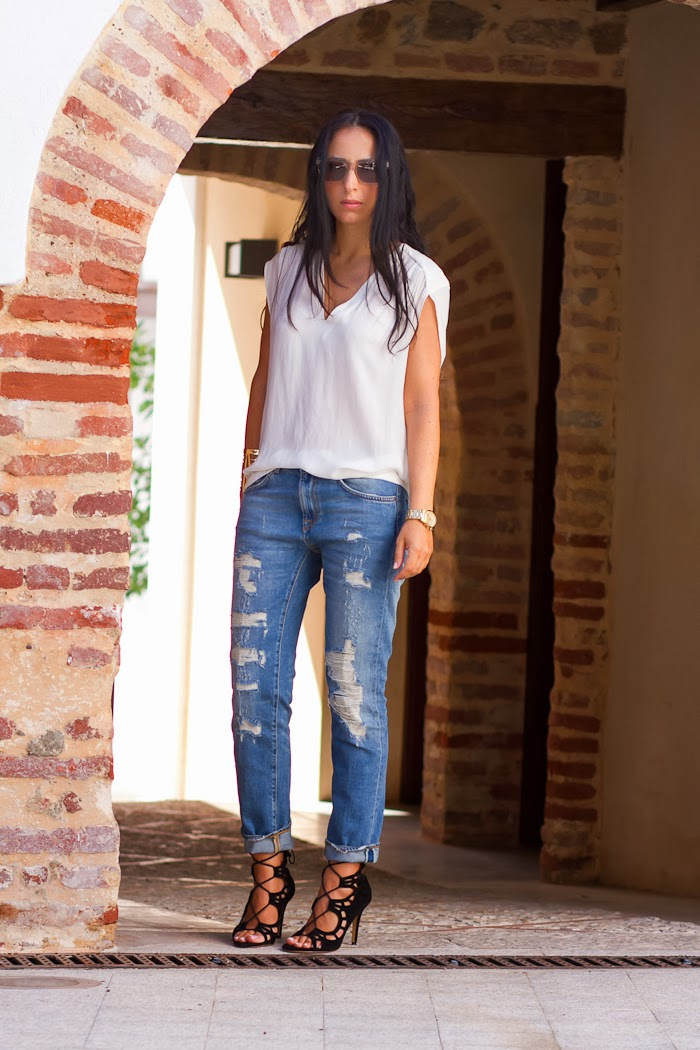 Blusa blanca, jeans rotos y sandalias acordonadas