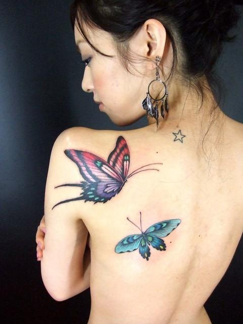 mujer asiatica de espaldas, vemos su tatuajes de mariposas en el omoplato y costado