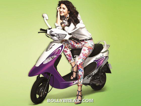 Anushka Sharma Riding Posing on a tvs scooty wearing floral skinny pants and a solid beige shirt  - Anushka Sharma TVS Scooty ad
