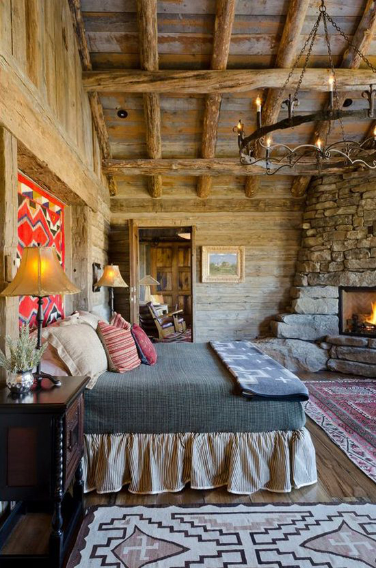 Cozy rustic log cabin bedroom with a stone fireplace