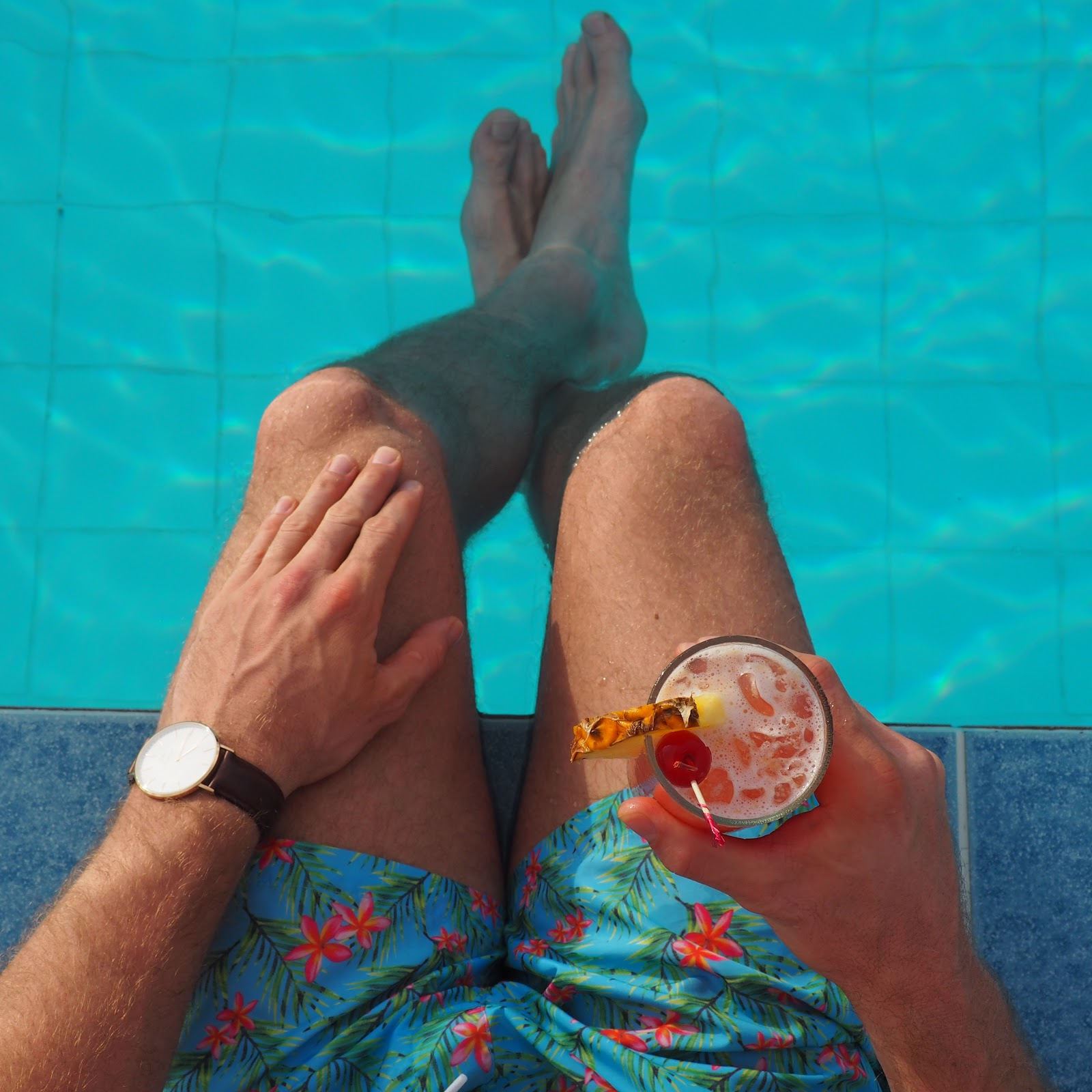 Man sitting by side of pool with cocktail in hand