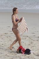 Heather Graham on a sandy beach holding a towel