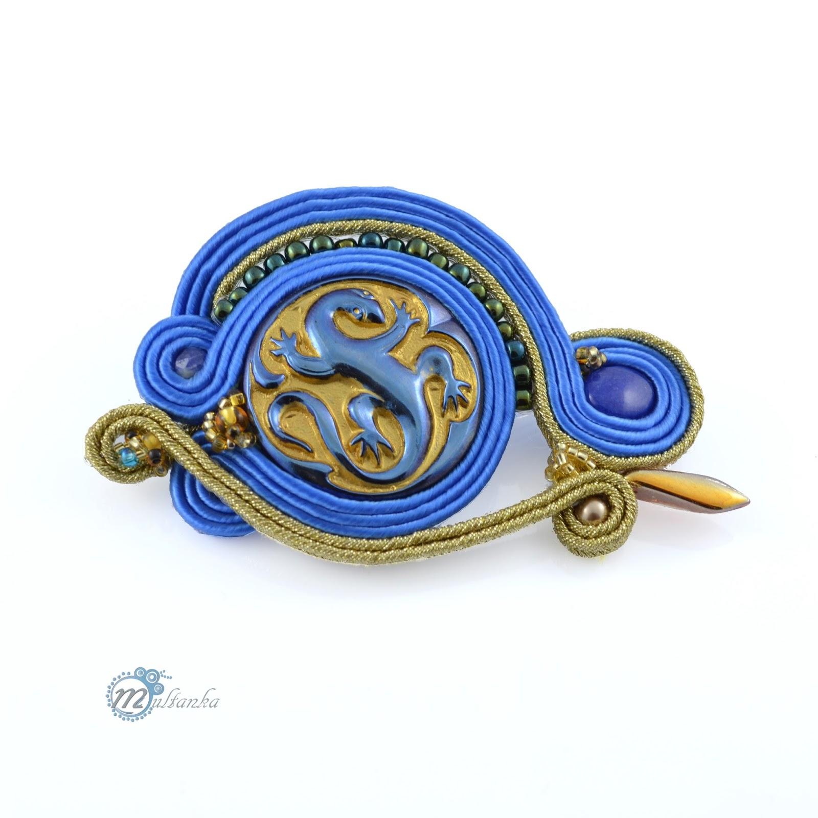 Granatowo-złota broszka z motywem jaszczurki wykonana metodą haftu soutache. Wykonanie - multanka.
