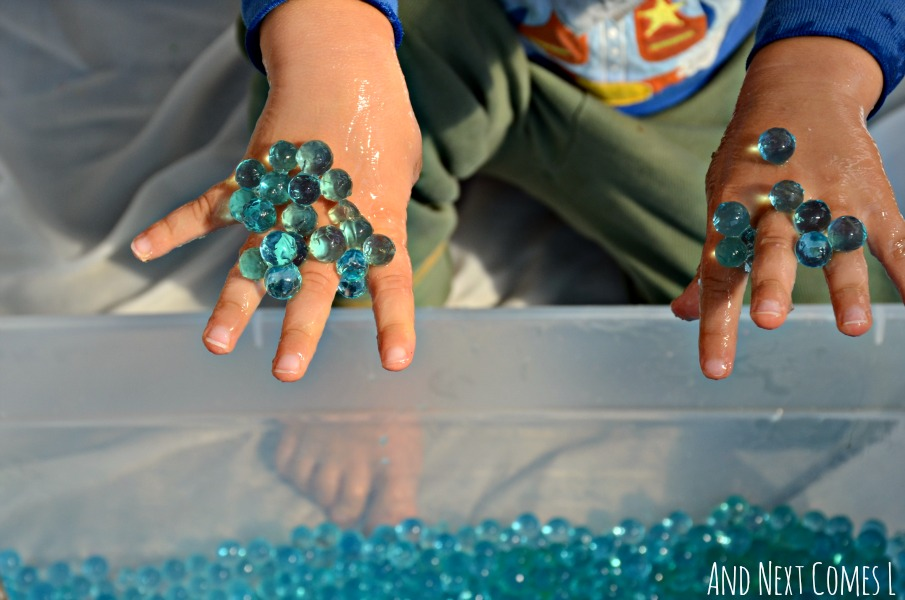 Playing with water beads and aloe vera gel in an Earth inspired sensory bin for kids from And Next Comes L