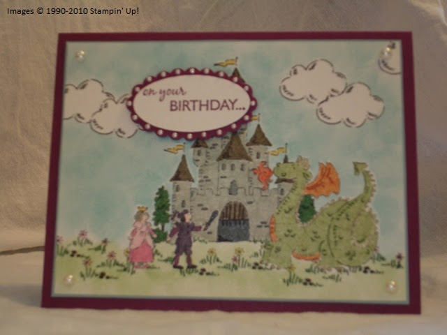 Card with a stamped and colored storybook scene: dragon in front of a castle, princess and a prince with his sword drawn.