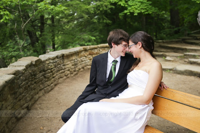 Young couple cuddling on bench on their wedding day