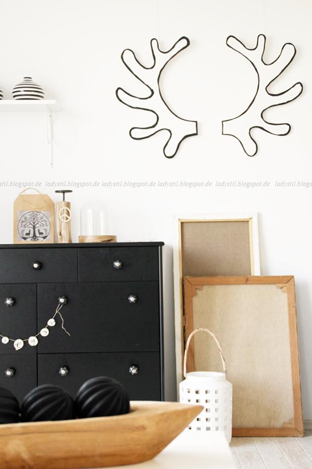 DIY Upcycling Geweih aus Holz in Weiß mit schwarzen Rändern über einer schwarzen Kommode mit weihnachtlicher Deko in schwarz weiß Holz