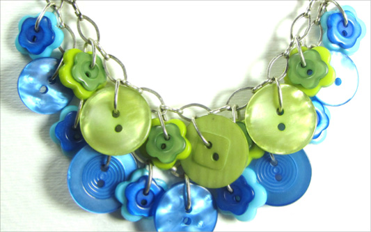 Layered necklace has green and blue fashion buttons and flower buttons on a pretty silver chain