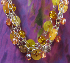 Three strand necklace has yellow beads and buttons mingling in shimmering twist style
