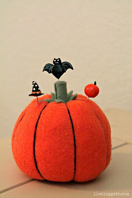 Pumpkin pincushion with handmade Halloween pins.