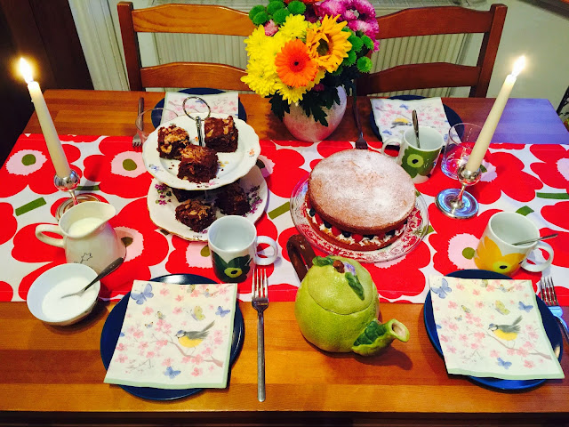 Table with birthday cakes, Victoria sandwich and sunflowers