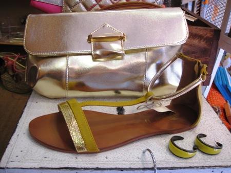 Cartera dorada tipo sobre y sandalia plana con pulsera.
