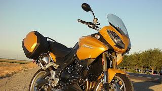 Oranje gouden motorfiets in de berm geparkeerd