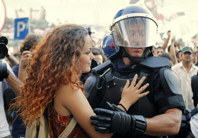 Демонстрантка обнимает полицейского во время акции протеста в Лиссабоне в 2012 году.