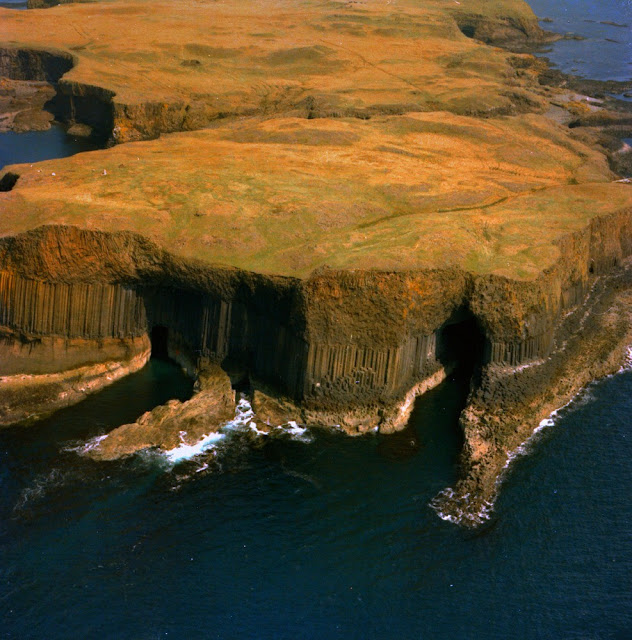 Oblique aerial view of The Great Face, the south end of the island of Staffa. Argyll and Bute. The Boat Cave is on the left and Fingal's Cave on the right. Massive, straight, well-formed columnar jointing in the Tertiary volcanic lava flow. The classic type of columnar jointing consists of a close-packed series of hexagonal 'prisms' lying perpendicular, in this case, to the base of the lava flow. Columnar jointing is formed by contraction during the cooling of the lava when a pattern of tensional forces acting towards a number of centres is set up. These forces tend to pull open a series of joints which ideally assume a hexagonal pattern.