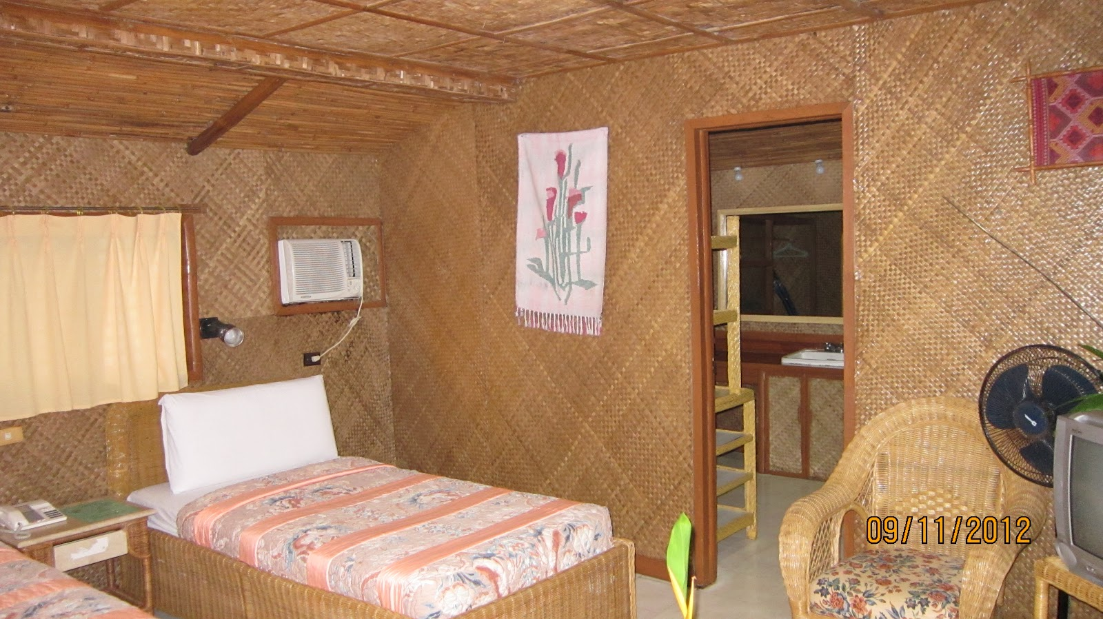 The room was what a dolled up nipa hut would look like wicker and rattan furniture yakan prints nardas weaves truth to tell it was bordering on gauche