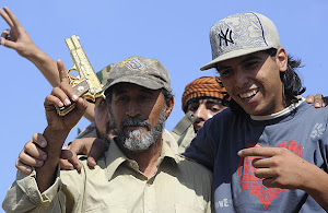 A man holds up what is thought to be Gaddafi's golden gun