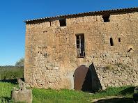 Façana de migdia del mas Sobirana on s'aprecia el portal adovellat, el massís contrafort, la finestra tapiada d'arc de mig punt i l'antiga galeria coberta amb tàpia