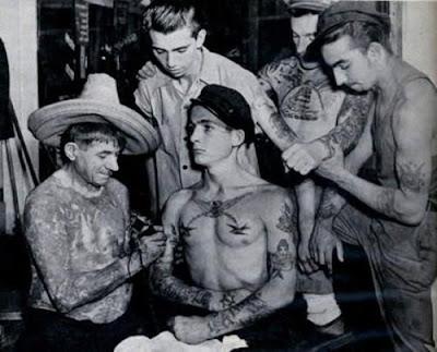 Alguns homens se tatuando.